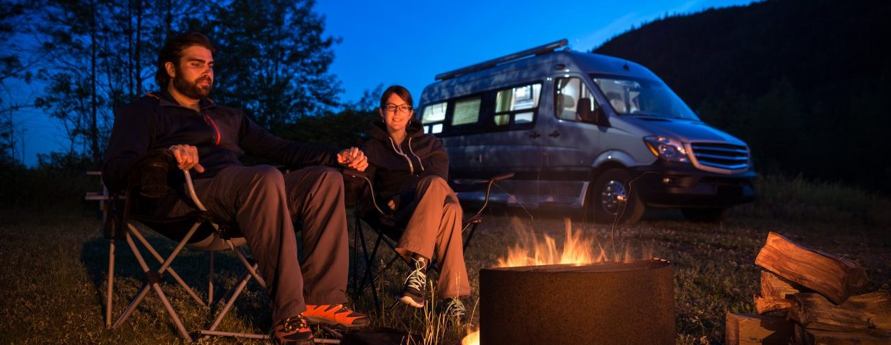 Couple Sitting Next to Campfire with Camper Van